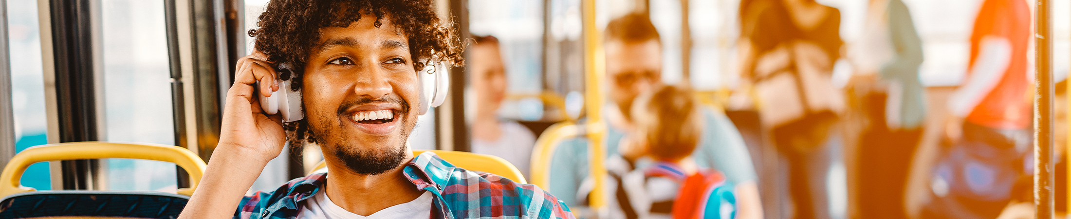 Young male riding the bus while listening music with his headphones